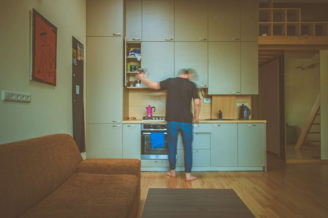 Man standing in front of dated kitchen cupboards that are teal and need a renovation
